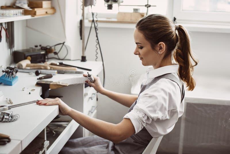Preparación de un lugar de trabajo Vista lateral del joyero de sexo femenino joven que prepara el lugar de trabajo para hacer la  imágenes de archivo libres de regalías