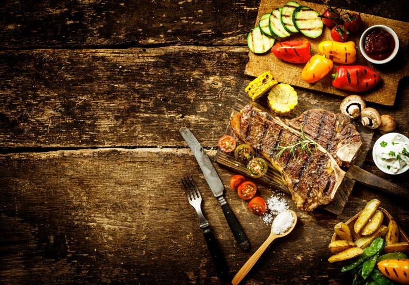 Preparación de verduras del filete y de la carne asada del t-hueso fotos de archivo