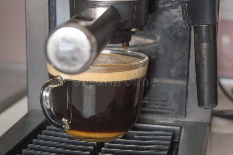 Preparación del café para el desayuno en un fabricante de café de la algarroba, una taza de café sólo con espuma imagen de archivo