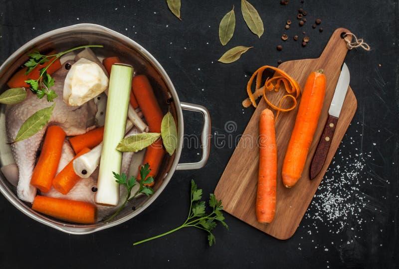 Preparación del caldo de pollo con las verduras (caldo) en un pote imagen de archivo