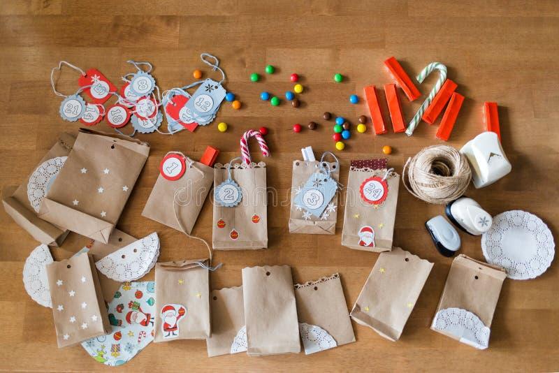 Preparación del calendario del advenimiento bolsos y dulces en la tabla idea de DIY para la Navidad fotografía de archivo libre de regalías