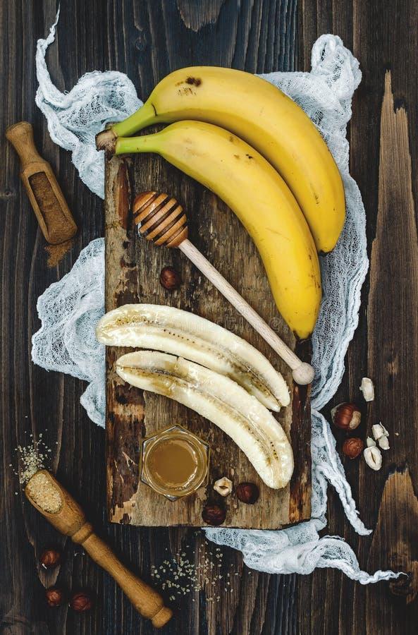 Preparación del cuenco sano del desayuno de la caída y del invierno Plátanos, cazo de la miel y avellanas caramelizados sobre el  imagen de archivo libre de regalías