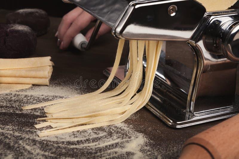 Preparación del fettuccine hecho en casa en la máquina de las pastas imagen de archivo