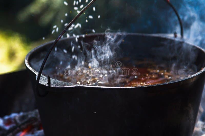 Preparación del pilaf en el fuego Jugador de bolos turístico con la comida en la hoguera, cocinando en el alza, al aire libre fotos de archivo