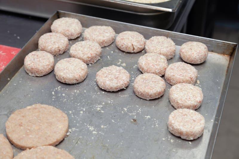 Preparación del primer de las chuletas del pollo para las hamburguesas Migas y mantequilla de pan en la tabla de cocina del metal fotografía de archivo