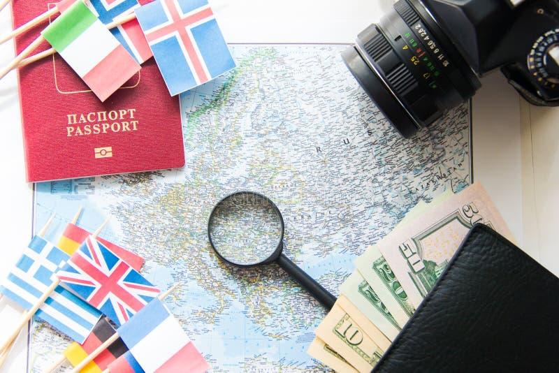Preparación del viaje: compás, dinero en la cartera, pasaporte, mapa de camino, lupa, cámara, banderas nacionales imagenes de archivo