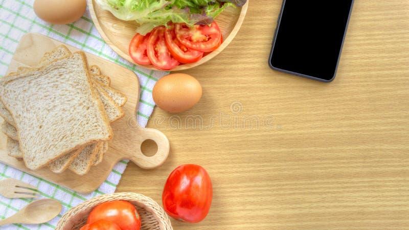 Preparación hecha en casa del desayuno del bocadillo El pan del trigo integral se apila en una tabla de cortar de madera puesta e fotos de archivo