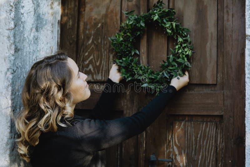 Preparación para la Navidad Guirnalda de la ejecución de la mujer joven en puerta imágenes de archivo libres de regalías
