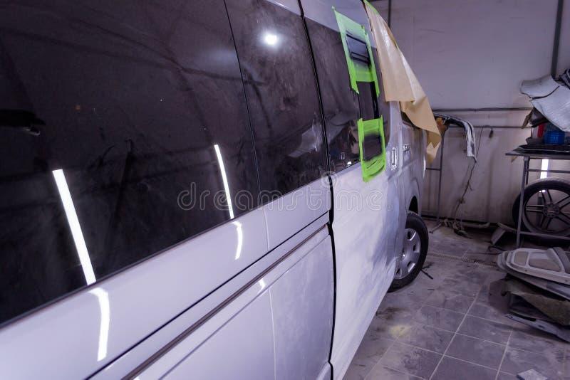 Preparación para pintar un autobús de plata en un taller de reparaciones del cuerpo en un s fotografía de archivo