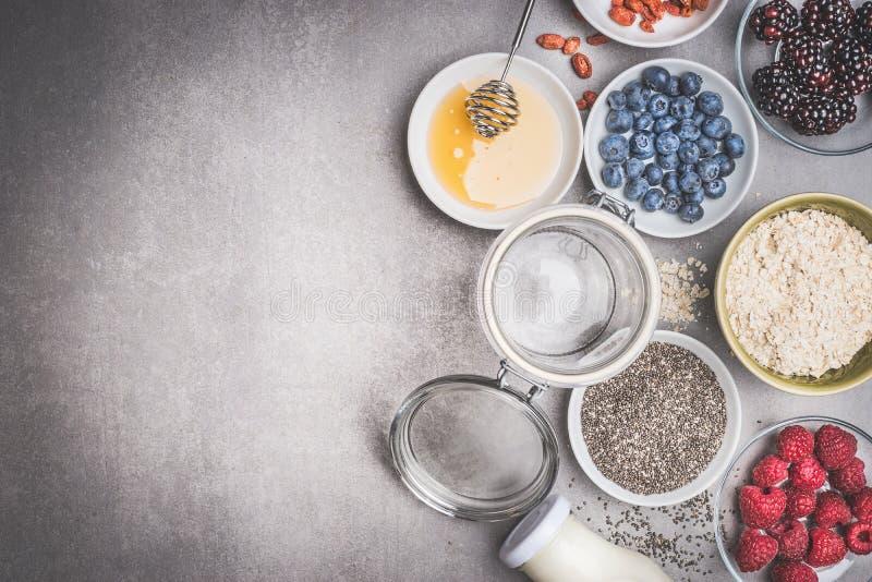 Preparación sana del desayuno con los ingredientes y el tarro de cristal vacío en el fondo de piedra, visión superior imagenes de archivo