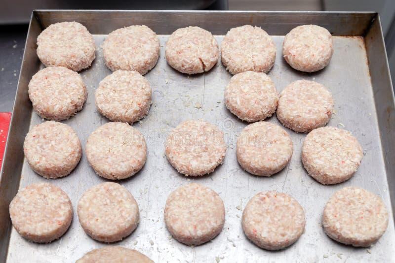 Preparaci?n del primer de las chuletas del pollo para las hamburguesas Migas y mantequilla de pan en la tabla de cocina del metal imágenes de archivo libres de regalías