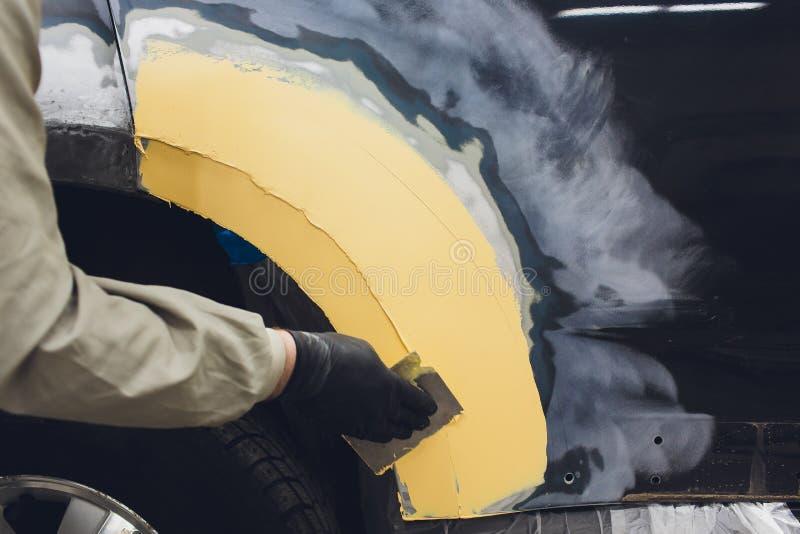 Preparaci?n para pintar un elemento del coche usando remitente del esmeril por un t?cnico del servicio que nivela hacia fuera ant foto de archivo libre de regalías