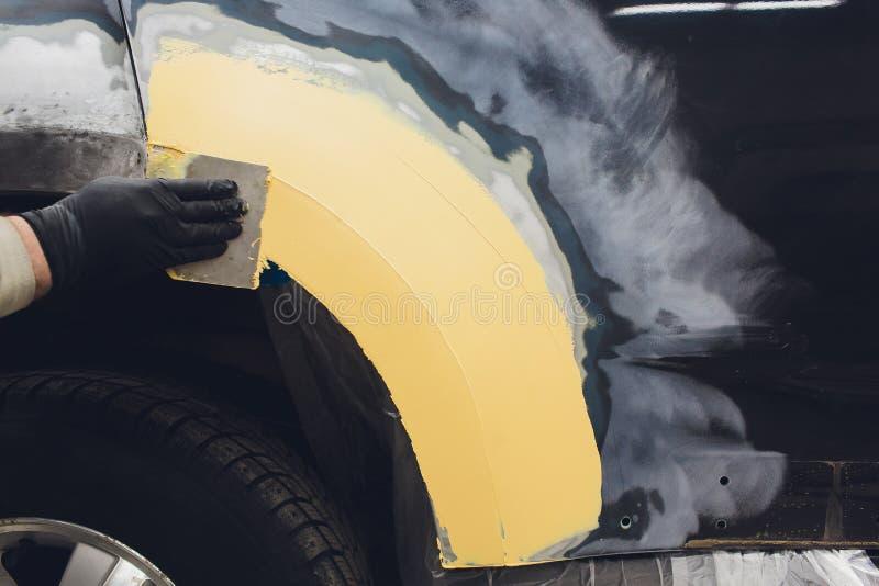 Preparaci?n para pintar un elemento del coche usando remitente del esmeril por un t?cnico del servicio que nivela hacia fuera ant imagen de archivo