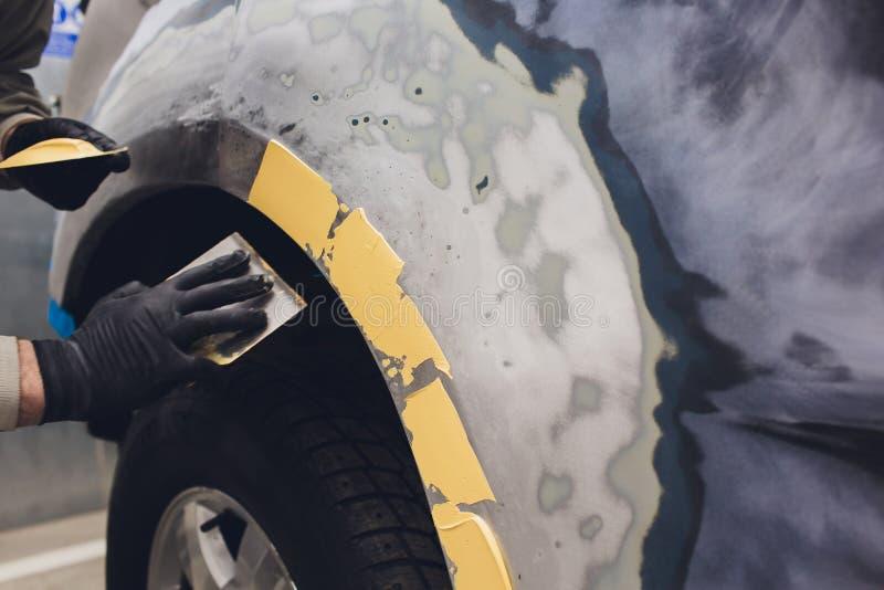 Preparaci?n para pintar un elemento del coche usando remitente del esmeril por un t?cnico del servicio que nivela hacia fuera ant fotografía de archivo
