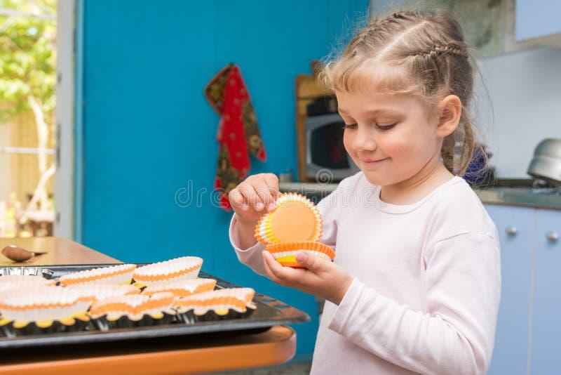 Preparan al niño para el banquete de Pascua, poniendo en las magdalenas de hornada de una Pascua de las latas fotografía de archivo