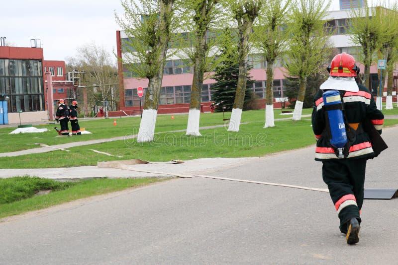 Preparan a los bomberos profesionales, a los salvadores en trajes incombustibles protectores, los cascos y las caretas antigás co imágenes de archivo libres de regalías
