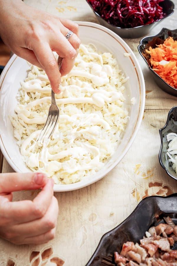 Preparando arenques tradicionais do ` da salada do russo sob o ` do casaco de pele imagens de stock