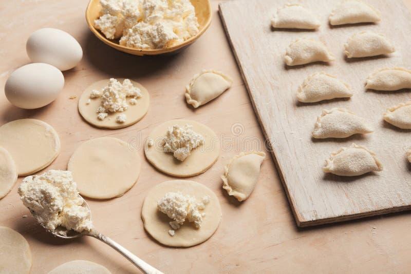 Preparando bolinhas de massa com o requeijão, cozinhando o alimento do russo foto de stock