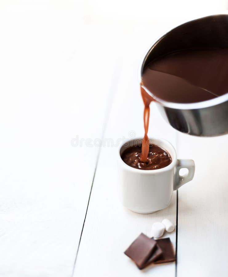 Preparando cioccolata calda - cioccolata calda scura scorrente da un vaso fotografia stock