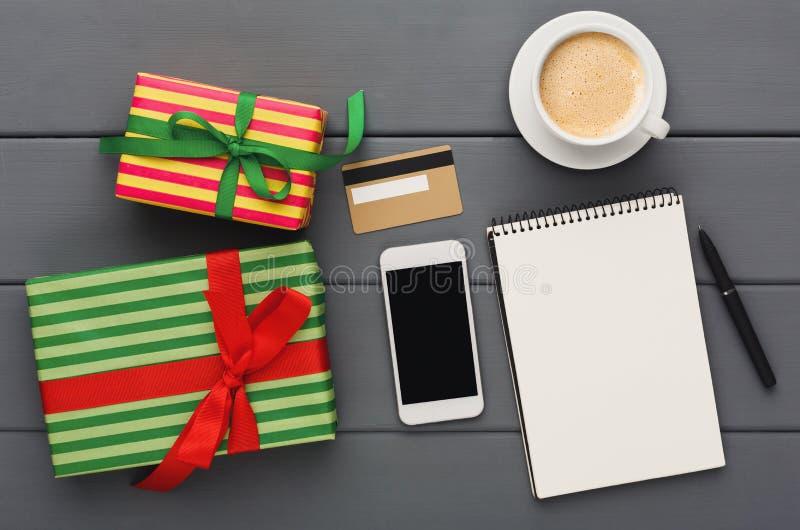 Preparando i regali per il natale, comperanti fondo online e di legno, vista superiore fotografia stock libera da diritti