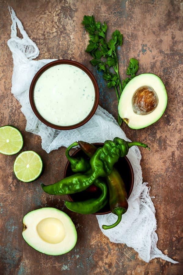 Preparando la salsa del coriandolo dell'avocado per i taci di pesce Calcini il crema in una ciotola su fondo di pietra d'annata fotografia stock libera da diritti