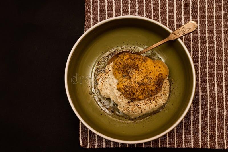 Preparando la salsa hecha de mostaza, de crema agria y de pimienta negra fotografía de archivo