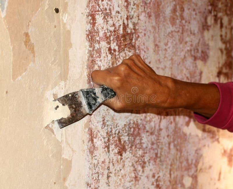 Preparando le pareti per la carta da parati con una spatola Riparazione nell'appartamento fotografie stock