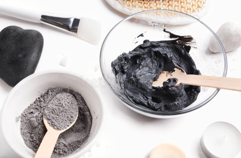 Preparando a máscara preta cosmética da lama na bacia de vidro imagens de stock royalty free