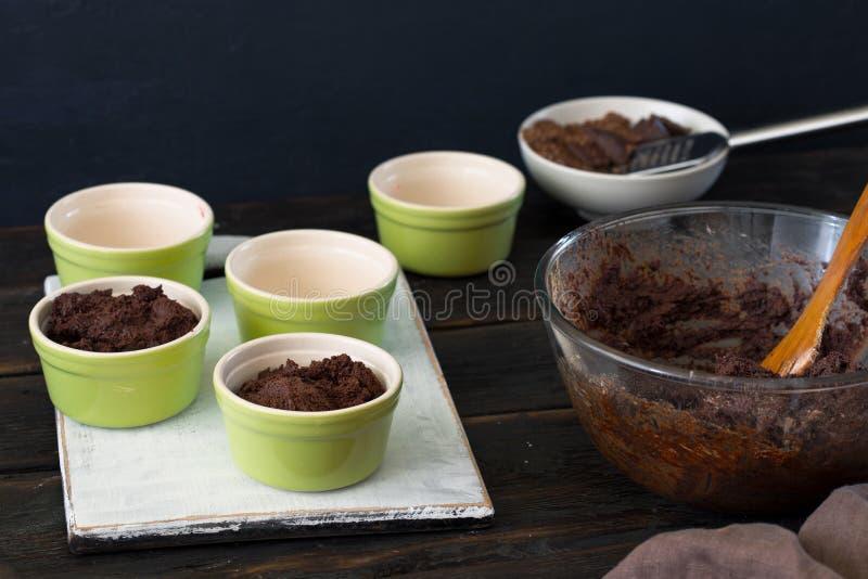 Preparando a massa para a torta do chocolate na tabela de madeira escura foto de stock