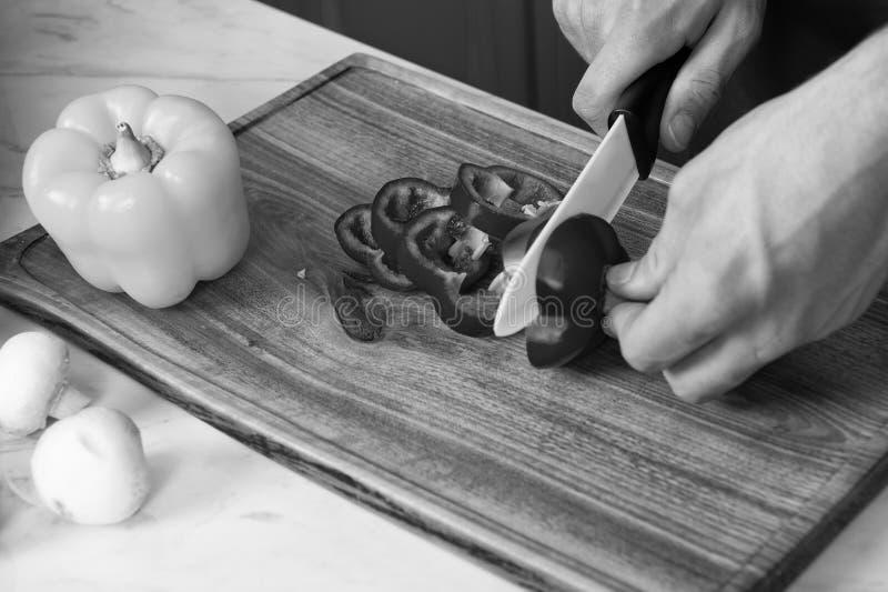 Preparando o alimento, cozinheiro chefe que corta a pimenta de sino vermelha fotografia de stock royalty free