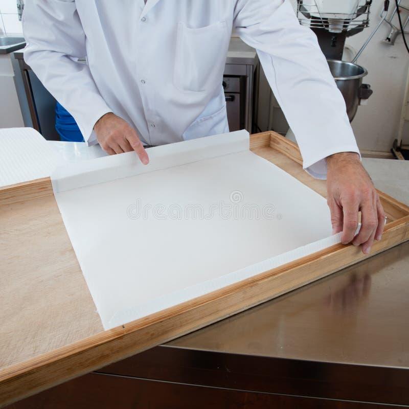 Preparando o quadro de madeira com papel de arroz como o molde para o nougat fotografia de stock