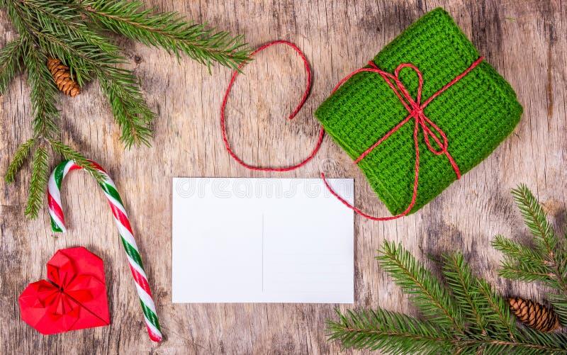 Preparando per il Natale Cartolina in bianco, biscotto dello zenzero e regalo tricottato sul bordo di legno anziano Copi lo spazi fotografia stock
