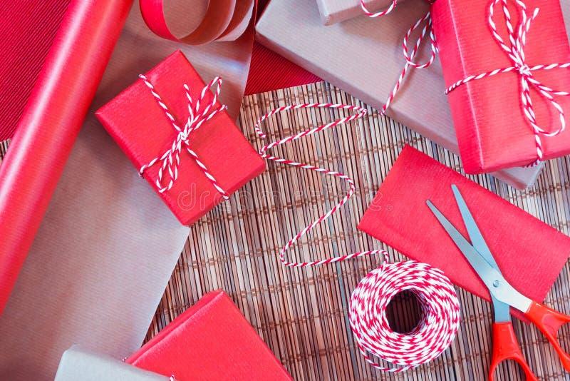Preparando per la festa - spostamento di regalo in carta da imballaggio rossa e beige immagine stock
