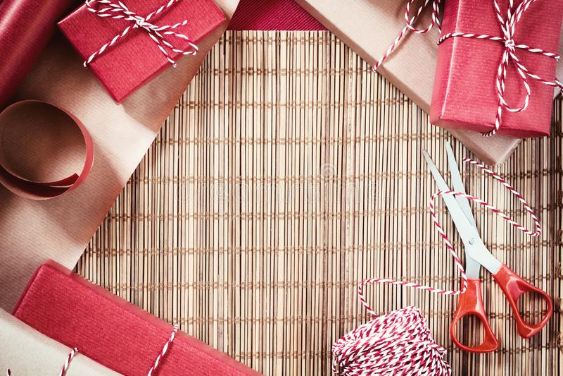Preparando per la festa - spostamento di regalo in carta da imballaggio rossa e beige immagine stock libera da diritti