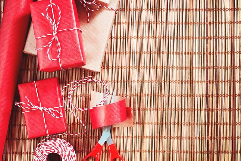 Preparando per la festa - spostamento di regalo in carta da imballaggio rossa e beige fotografie stock libere da diritti