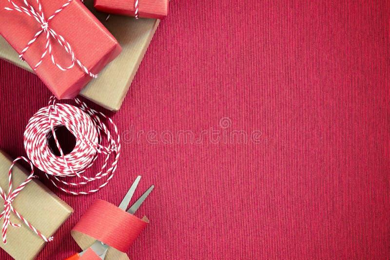 Preparando per la festa - spostamento di regalo in carta da imballaggio rossa e beige fotografie stock