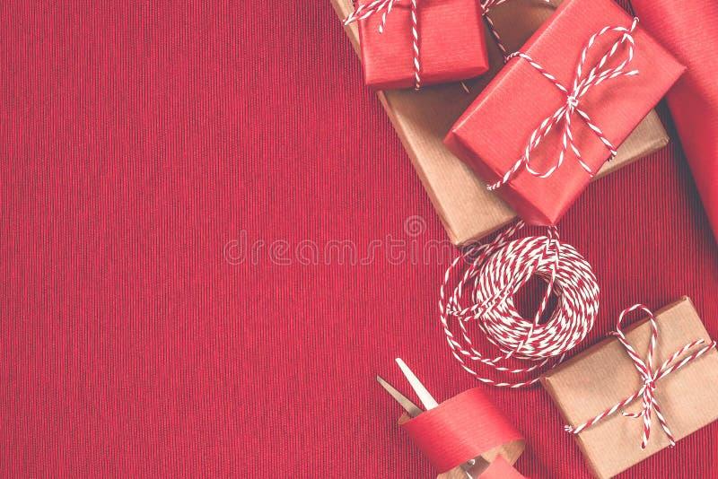 Preparando per la festa - spostamento di regalo in carta da imballaggio rossa e beige fotografia stock libera da diritti