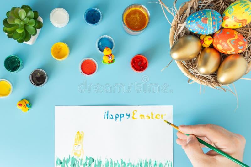 Preparando-se para a Páscoa, a cesta com os ovos da páscoa feitos à mão ao lado das pinturas multicoloridos e a mão com escova qu imagem de stock
