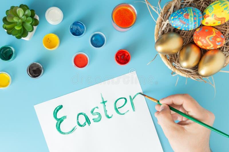 Preparando-se para a Páscoa, a cesta com os ovos da páscoa feitos à mão ao lado das pinturas multicoloridos e a mão com escova qu fotos de stock royalty free