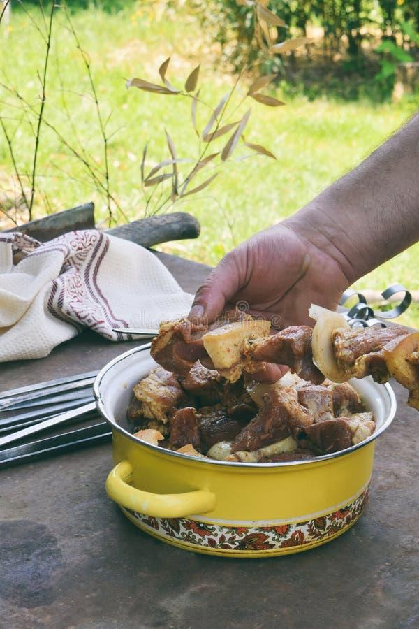 Preparando shashlik per la griglia del barbecue Una mano dell'uomo mette i pezzi di carne marinata sullo spiedo Kebab sugli spied immagine stock libera da diritti