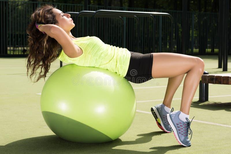 Preparandosi sulla palla di misura La giovane donna che fa gli sport si esercita sulla palla per prepararsi immagini stock libere da diritti