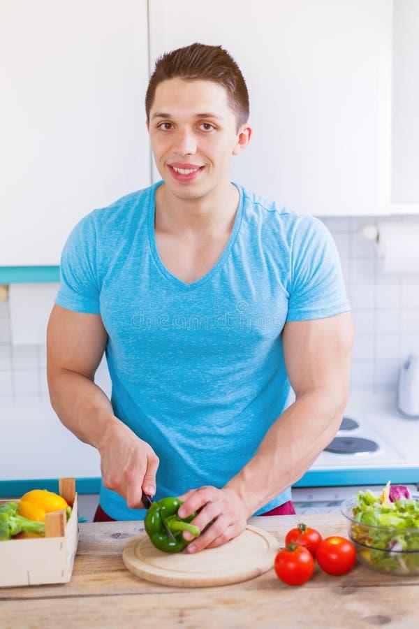 Preparar o alimento cortou a refeição saudável do homem novo dos vegetais no kitc imagem de stock royalty free