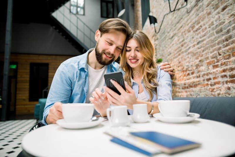 Prepararsi per il viaggio con un caffè Una felice coppia seduta al tavolo, bevendo caffè o tè, al telefono fotografia stock