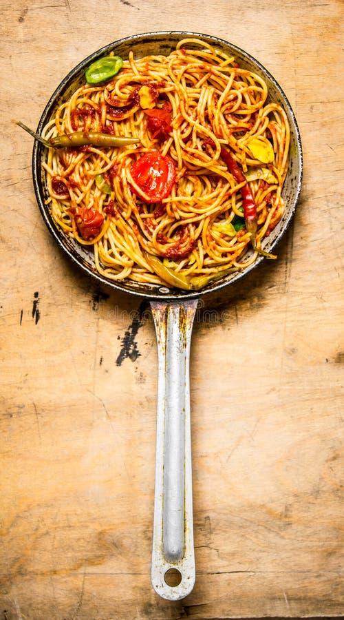 Preparated spagetti i tomatsås med kryddor i pannan arkivfoto