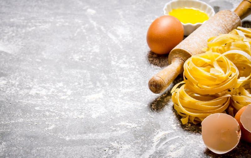 Preparated torr pasta med en kavel och ägg fotografering för bildbyråer