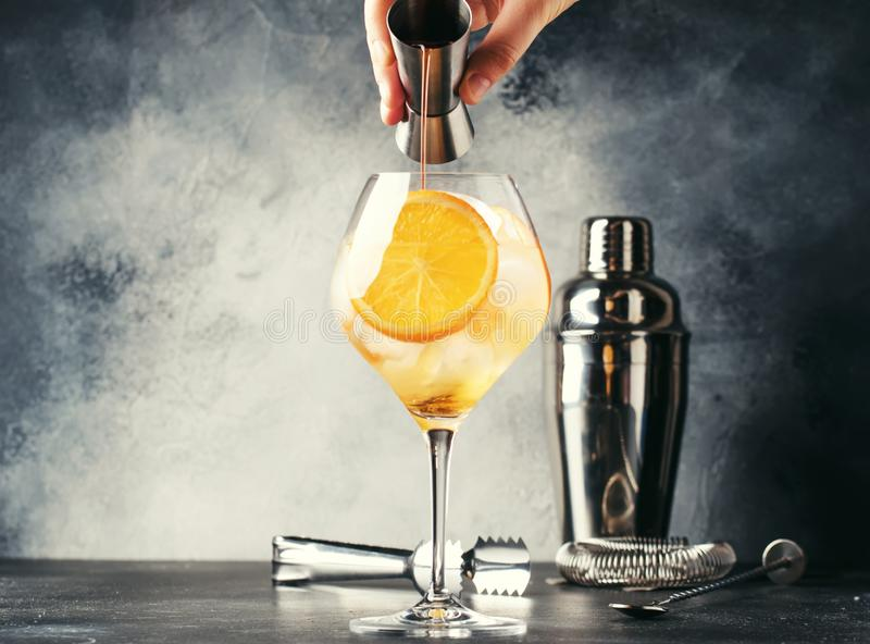 Preparation of Aperol spritz cocktail, barman pours bitter from jigger, summer Italian low-alcohol cold drink, black bar counter. Background, summer mood royalty free stock photo