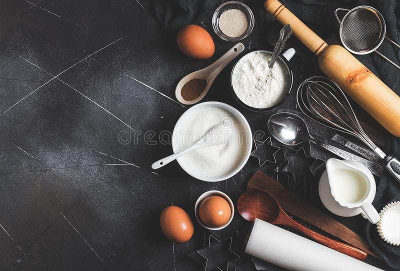 Preparation baking kitchen ingredients for cooking. Grocery accessories. For home pastry eggs flour sugar yeast milk spoon whisk for cooking food on dark stock photo