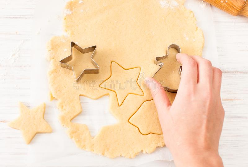 Cut the cookie shape from the dough at the white table. View with copy space royalty free stock image