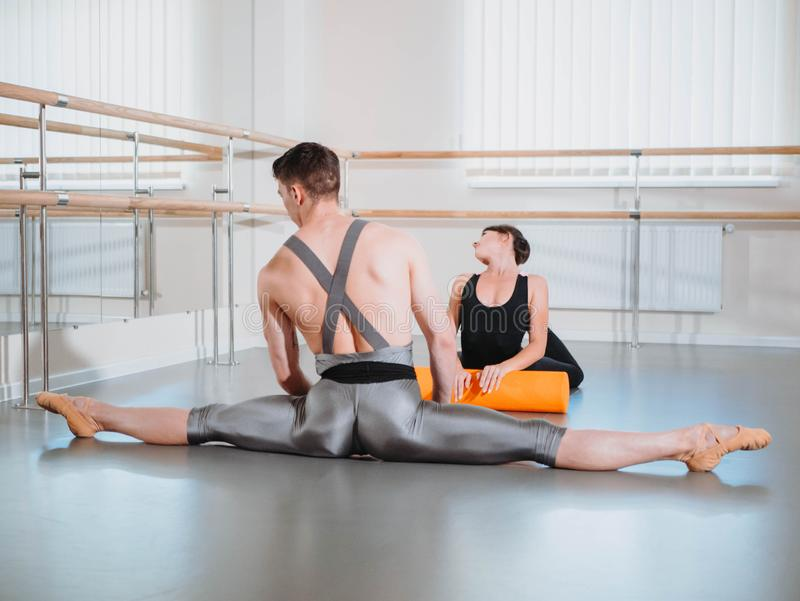 Preparation of body before performance in ballet studio. Male dancer and ballerina warming up near barre on rehearsal royalty free stock image