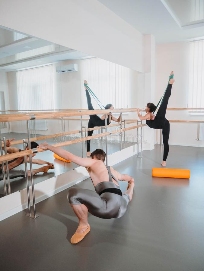 Preparation of body before performance in ballet studio. Male dancer and ballerina warming up near barre on rehearsal royalty free stock photo